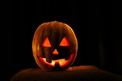 Funny Halloween pumpkin isolated on a black background glow from the inside