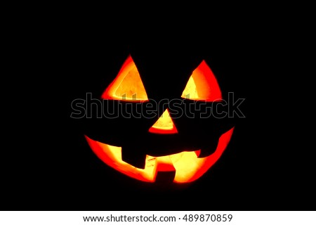 funny halloween pumpkin isolated on a black background glow from the