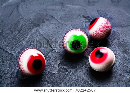 Funny halloween treat - jelly eyeballs on dark background. Copy space