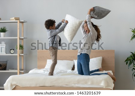 Funny happy african mixed race ethnicity family mum and little cute son having fun pillow fight on bed, young mother laughing playing funny game enjoy leisure activity with small child boy in bedroom