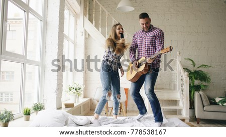 Funny happy and loving couple dance on bed singing with tv controller and playing guitar. Man and woman have fun during their holiday at home #778538167