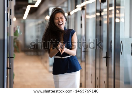 Funny happy asian business woman winner feel overjoyed standing in office hallway laughing screaming celebrate professional win, excited by victory success corporate reward career promotion concept