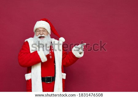 Funny happy excited old bearded Santa Claus face wearing costume looking at camera showing pointing fingers aside advertising Christmas promotion, New Year xmas discount ad isolated on red background.