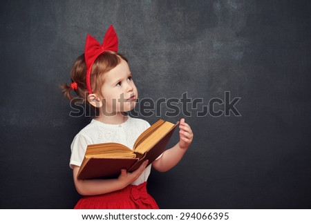 funny happy little girl schoolgirl with a book from the blackboard