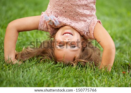 Funny happy little girl standing on her head on the grass in the park. Childhood concept, ready for your text, logo or symbols.