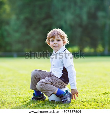 Funny happy little kid boy of 4 resting after playing soccer with football on football field, outdoors. Active leisure and lifestyle with little children
