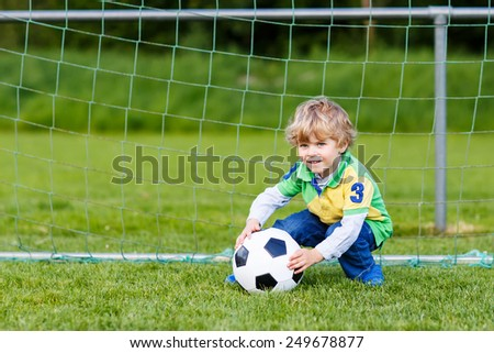 Funny happy little kid boy playing soccer and football and having fun, outdoors on field. Active leisure with children on warm sunny summer day.