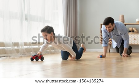 Funny happy male family young adult dad and cute excited little kid son pretending racing on warm wooden floor at home, father having fun chasing small preschool child boy playing cars together