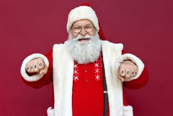 Funny happy old bearded Santa Claus wearing hat, glasses, costume looking at camera showing fists gesture 2020 2021 tattoo celebrating Merry Christmas, New Year isolated standing on red background.