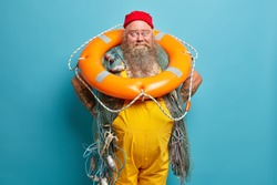 Funny happy sailor dressed in red hat and yellow overalls keeps hands on waist stands with inflated lifering fishing equipment has sea adventure at deck isolated on blue wall. Plump tattooed boatswain