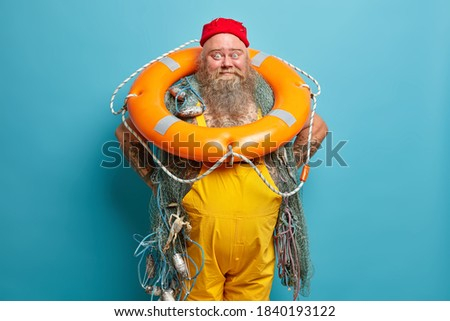 Funny happy sailor dressed in red hat and yellow overalls keeps hands on waist stands with inflated lifering fishing equipment has sea adventure at deck isolated on blue wall. Plump tattooed boatswain Stok fotoğraf ©