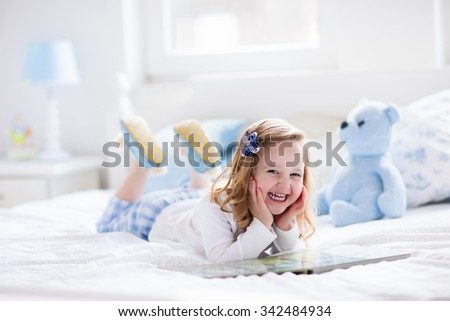 Funny happy toddler girl reading a book and playing with her toy teddy bear in bed. Kids play at home. White nursery. Child in sunny bedroom. Children read and study. Interior for baby and young kid.