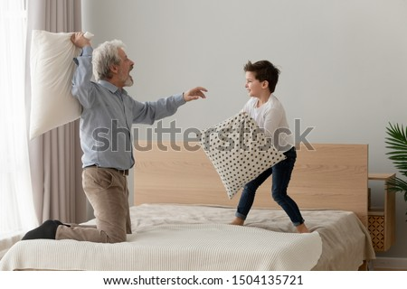 Funny happy two generation men family old grandfather and little cute grandson having fun pillow fight on bed, senior grandpa playing funny game enjoy leisure activity with grandchild boy in bedroom
