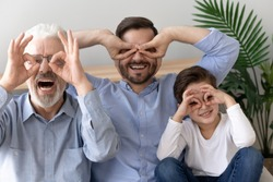 Funny head shot portrait grandfather, father and little son, three generations, happy granddad, dad and preschool grandchild boy making glasses with fingers, looking at camera, posing for photo