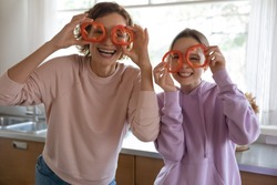 Funny healthy vegan family make pepper glasses having fun cooking together in kitchen. Happy young mum and cute teenage daughter preparing vegetarian food meal, laughing, looking at camera, portrait.