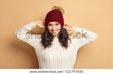 Funny Hipster Girl in Knitted Sweater and Beanie Hat over beige soft Background. Trendy Casual trendy young woman in winter outfit #521797660