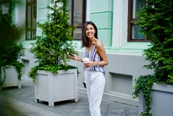 Funny hipster girl with disposable caffeine beverage and cellular gadget rejoicing at street enjoying coffee break during summer daytime, happy female travel blogger with smartphone smiling outdoors