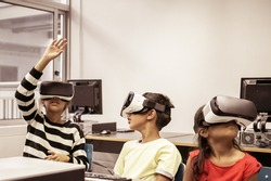 Funny Hispanic children sitting at table and using VR headsets. Cute little girl rising hand up. Cute multiethnic kids watching virtual reality in computer school. Informatics and education concept