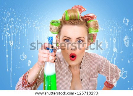 Funny housewife / woman behind window spraying the cleaner on glass, foam / soap on glass
