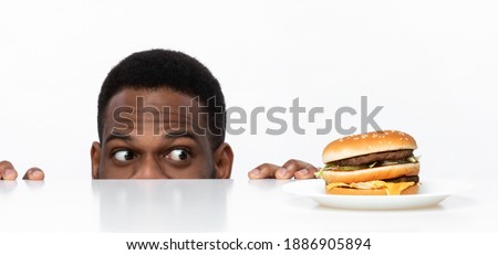 Funny Hungry African Guy Looking At Tasty Burger On Desk Having Food Craving Posing In Studio On White Background. Overeating Habit, Dieting And Nutrition, Cheat Meal Concept. Panorama Photo stock ©