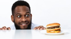 Funny Hungry Black Man Looking At Burger On Table Posing Over White Studio Background. Nutrition And Dieting, Cheat Meal And Unhealthy Junk Food, Overeating Habit Concept. Panorama