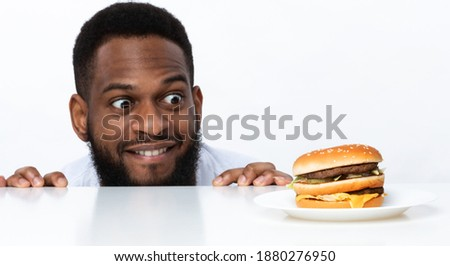 Funny Hungry Black Man Looking At Burger On Table Posing Over White Studio Background. Nutrition And Dieting, Cheat Meal And Unhealthy Junk Food, Overeating Habit Concept. Panorama Photo stock ©