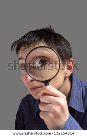 Funny image of a adult woman with a magnifying glass, one eye is enlarged.