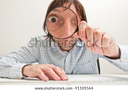 Funny image of a business person with a magnifying glass, one eye is enlarged.