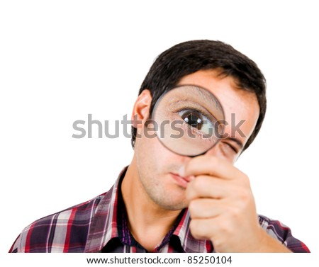 Funny image of a young man looking through magnifying glass. ( focus on the left eye )