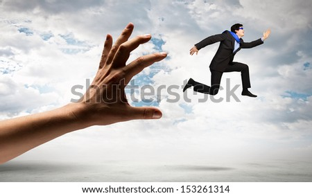 funny image of businessman trying to run away from hand