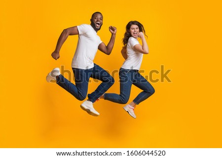 Funny interracial couple jumping in the air, running fast to big sales, hurry to come in time, posing together on yellow background with free space