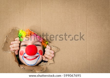 Shutterstock Funny kid clown looking through hole on cardboard. Child playing at home. 1 April Fool's day concept. Copy space.