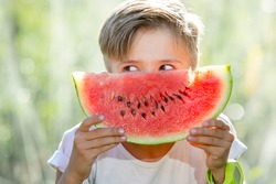 Funny kid eating watermelon outdoors in summer park, focus on eyes. Child, baby, healthy food