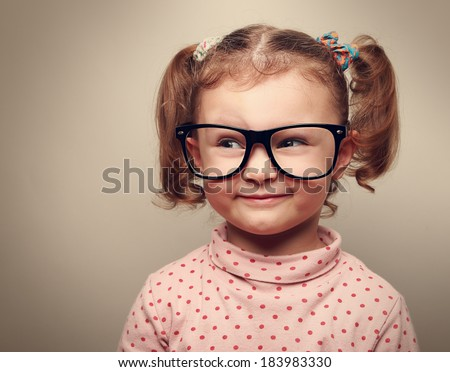 Funny kid girl in glasses looking on empty copy space and thinking. Instagram effect