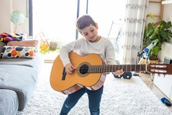 Funny kid playing guitar at home
