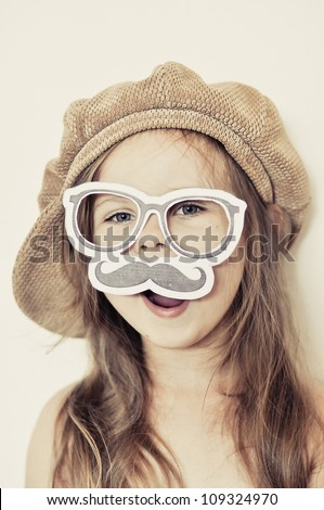 Funny kid wearing a fake mustache and cap