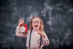 Funny kid with alarm clock. Stressed kid worried about deadline. Little girl holding red clock in hand. Reminder Time to go Back to school. Meeting or breaking deadline. Instagram filter