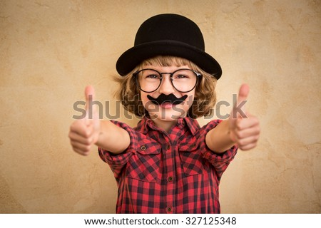 Funny kid with fake mustache. Happy child playing in home