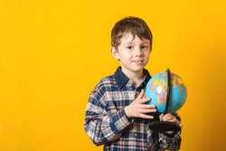 Funny kid with globe, isolated on yellow. Back to school concept. Educational globe. Curious child holding earth globe map in his hand. Little traveler, exploring new horizons at globe. Copy space.