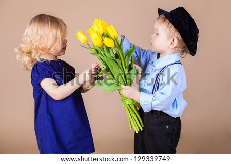 Funny kids, happy little boy giving a cute girl bouquet of yellow spring flowers. Series in studio. Valentines Day
