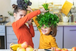 Funny kids make green smoothies while having fun. Happy sister and brother helping in the kitchen, laughing, opens the lid of the blender. Fun vegan family cooking activities. Healthy Eating Concept