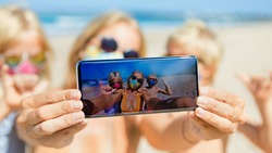 Funny kids with mother taking selfie photo by smartphone on tropical sea beach. Rule to wear face covering mask at public places due coronavirus COVID 19. Family holidays with children, summer travel.