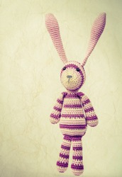 Funny knitted rabbit toy portrait with ears up, vintage toned photo with instagram retro style toned effect and old paper texture