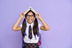 Funny latin schoolgirl in glasses holding book on her head having fun teasing with tongue. Portait of adorable happy indian teenage looking at camera isolated on violet background.