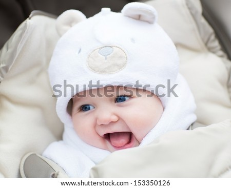 Funny laughing baby in a teddy bear hat sitting in a stroller on c old winter day