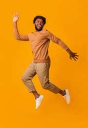 Funny laughing black guy jumping in the air over orange background