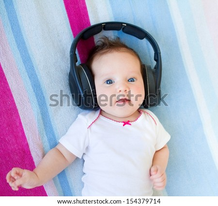 Funny laughing newborn baby relaxing on a colorful blanket listening to music with huge earphones