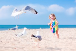 Funny laughing toddler, adorable little girl with curly hair in a colorful dress playing with seagull birds, running and jumping on a beautiful beach on a sunny hot summer day