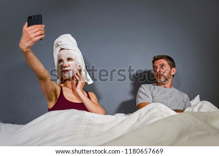 funny lifestyle portrait of eccentric housewife with makeup facial mask and towel taking selfie in bed and husband with desperate face expression in weird man woman relationship concept
