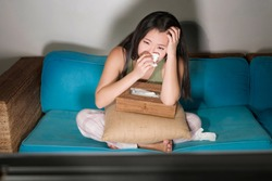 funny lifestyle portrait of young cute and emotional Asian Chinese woman watching korean drama show on TV sitting at home living room couch crying wiping tears with tissue paper